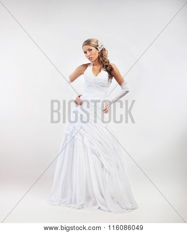 Full-length portrait of gorgeous bride wearing wedding dress and flower alike accessories over grey background.