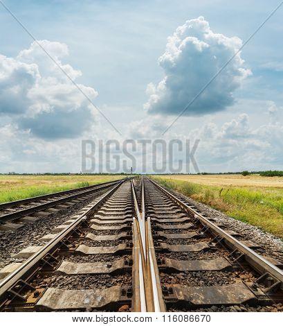 crossing of railways closeup under cloudy sky