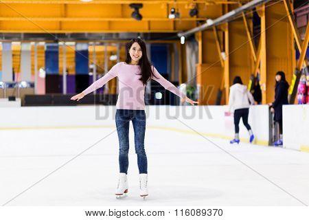 Young woman make balance on skating rink