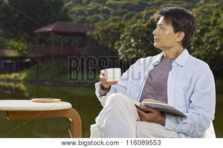 Man Gazing Afar When Reading Outdoor