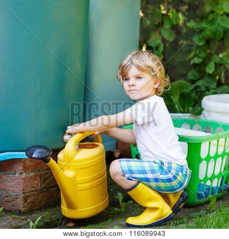 little kid boy watering plants in garden in summer