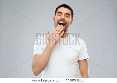 yawning man over gray background