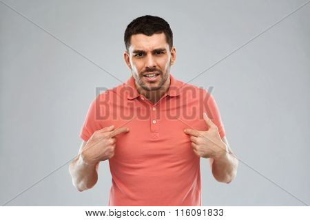 angry man pointing finger to himself over gray