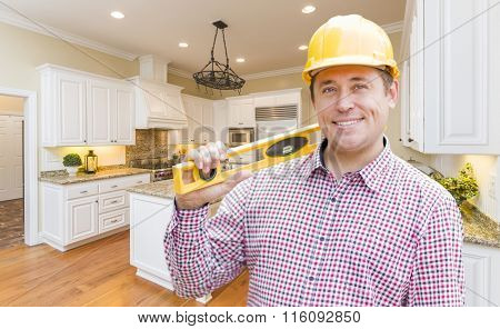 Smiling Contractor with Level Wearing Hard Hat Standing In Custom Kitchen.