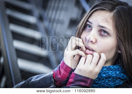Young Badly Bruised and Frightened Girl on Staircase.