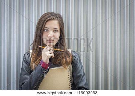 Pretty Young Melancholy Female Student With Books and Pencil Looking to the Side.