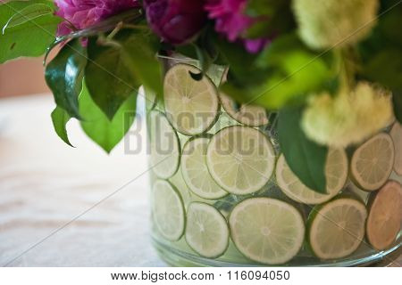 Vase with lime and flowers against a white tablecloth