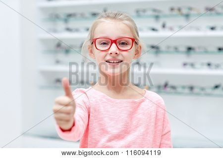 girl in glasses at optics store showing thumbs up