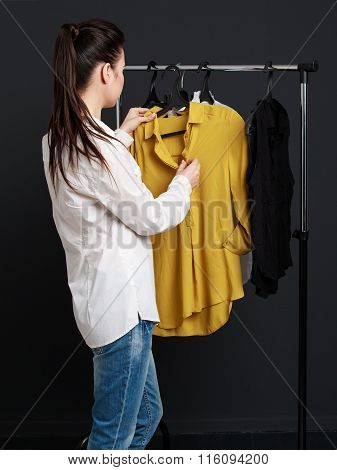 The Customer Chooses The Clothes. Young Woman In White Blouse And Blue Jeans Is Considering A Yellow