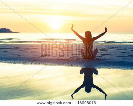 Silhouette of the woman sitting on the beach during amazing sunset, with reflection in the water. Health and Yoga exercises.