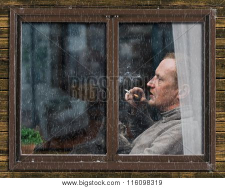 Rain, the window of the apartment. Outside, the profile of a man with a cat in her arms