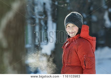Head and shoulders winter outdoor portrait of cheerful teenage boy breathing with visible steam mout