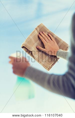 close up of woman hands cleaning window with cloth
