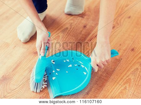 close up of woman with brush and dustpan sweeping