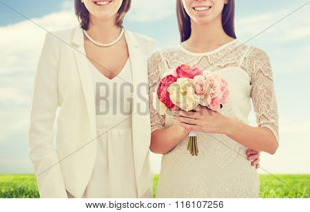 close up of happy lesbian couple with flowers