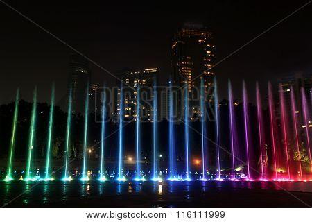 Illuminated fountain at night in modern city skyline, Kuala Lumpur