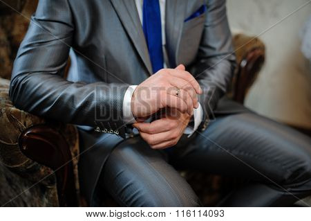 Man In A Suit Sitting In A Chair And Puts Cufflinks