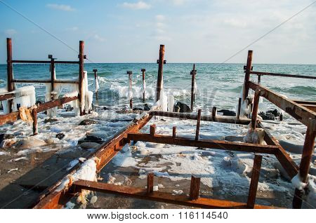 Frozen winter sea with wooden pole. Horizontal