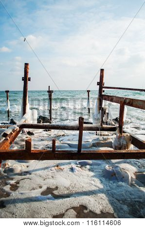 Frozen winter sea with wooden pole. Vertical