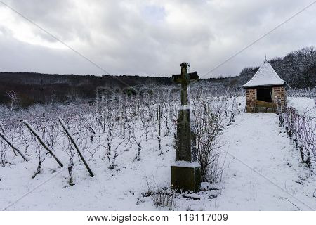 Religious Cross In Winter Snowy Vineyard