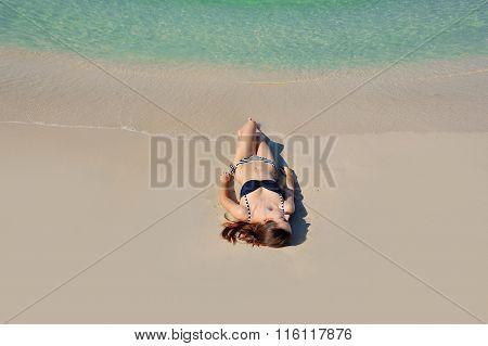 Beautiful Girl Sunbathes On A Beach Alone