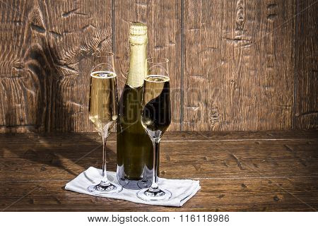 Bottle And Two Glasses Of Champagne Are Standing On A White Napkin Are Stand On Old A Table