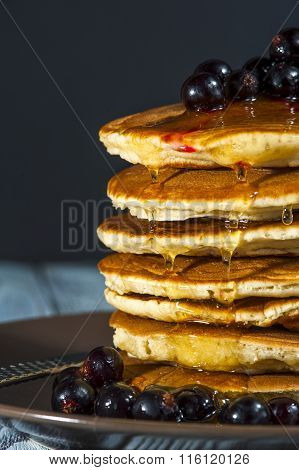 Stack of homemade pancakes with berries and honey on brown plate on rustic background.