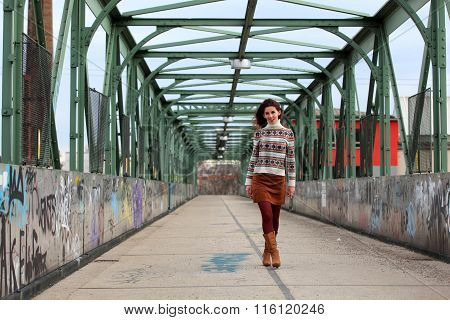 Walking girl wearing pullover, boots and mini skirt
