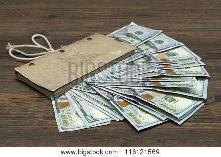 Vintage Notebook With Dollar Cash On Wood Background