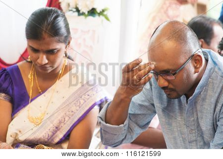 Hindu man putting tilak or marking on his forehead during Indian traditional religious rituals, the tradition of Hinduism.