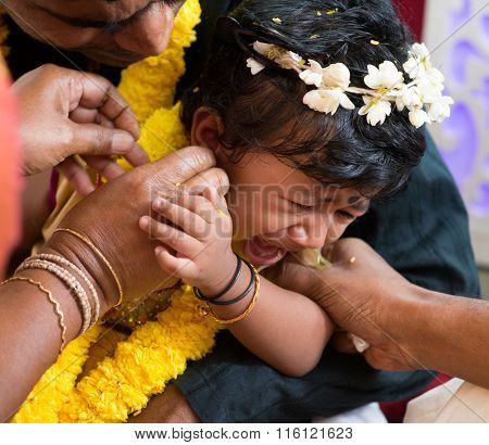 Baby girl crying during the karna vedha events. Traditional Indian Hindus ear piercing ceremony. India special rituals.