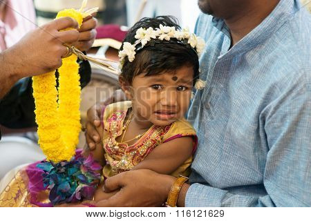 Baby girl received flower garland from priest. Traditional Indian Hindus ear piercing ceremony. India special rituals.