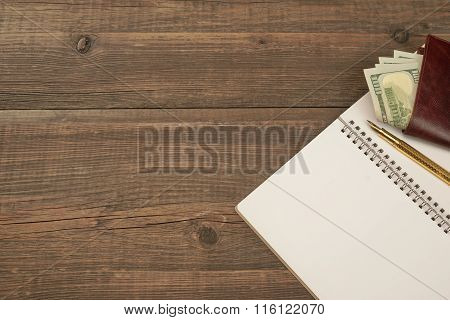 Opened Spiral Notepad,  Wallet With Dollar Cash, Pen On Wood