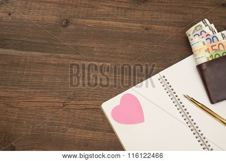 Wedding Costs Concept. Hearts, Pen, Paper, Money On Wood Background