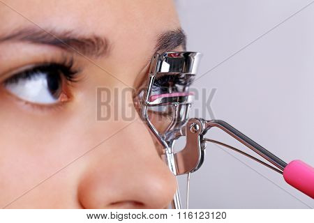 Woman corrects eyelashes with curling tongs, close up