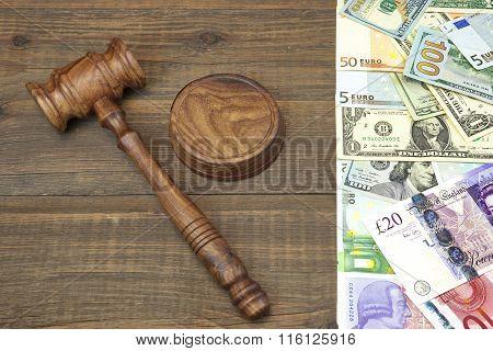 Judges Gavel And International Money On Rough Wood Background.