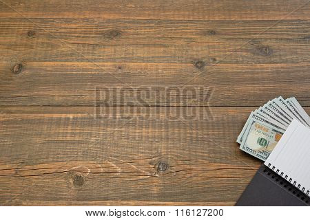 Notepad With Dollar Cash On The Brown Wood Background