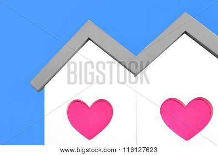 White House With Two Pink Heart Window On Blue Background