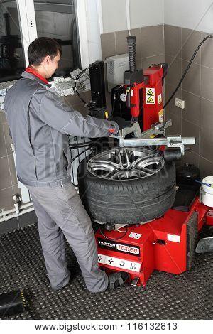 Car Service. The Worker Balances Repair A Tire