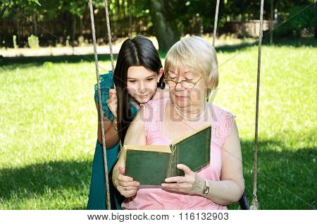 Teen Girl And Her Grandmother Read A Book In The Park Horizontal