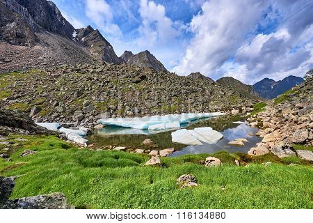 Alpine Meadow With Green Onions At A Small Lake With Ice