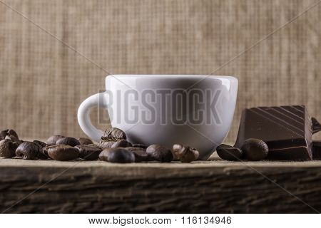 Cup, coffee beans, chocolate on a wooden Board closeup background