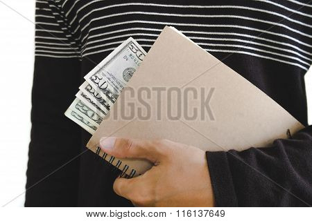 A man holding book with cash hiding inside, isolated on white background