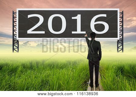 Business Man Standing On Wood Bridge Between Rice Field And Pointing With Large Sign Of 2016