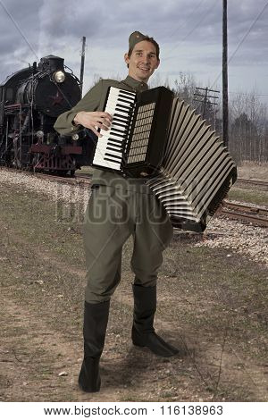 Soviet Soldier With An Accordion Outdoors