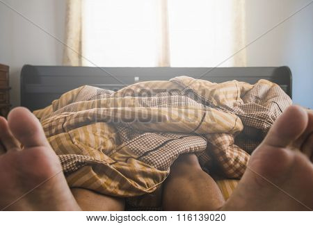 Man sleeping under blanket on bed in the morning
