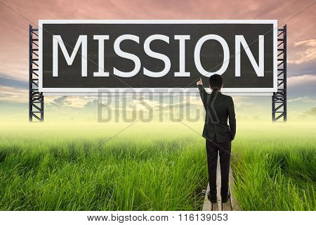 Business Man Standing On Wood Bridge Between Rice Field And Pointing With Large Sign Of Mission