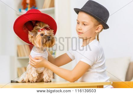 Little girl is dressing her dog up.