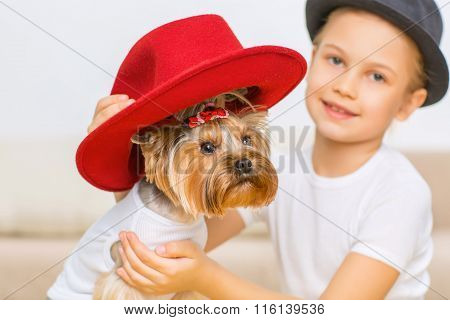 Little girl is putting red hat on her dog.