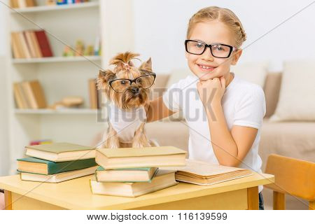 Little girl and her dog wearing glasses.
